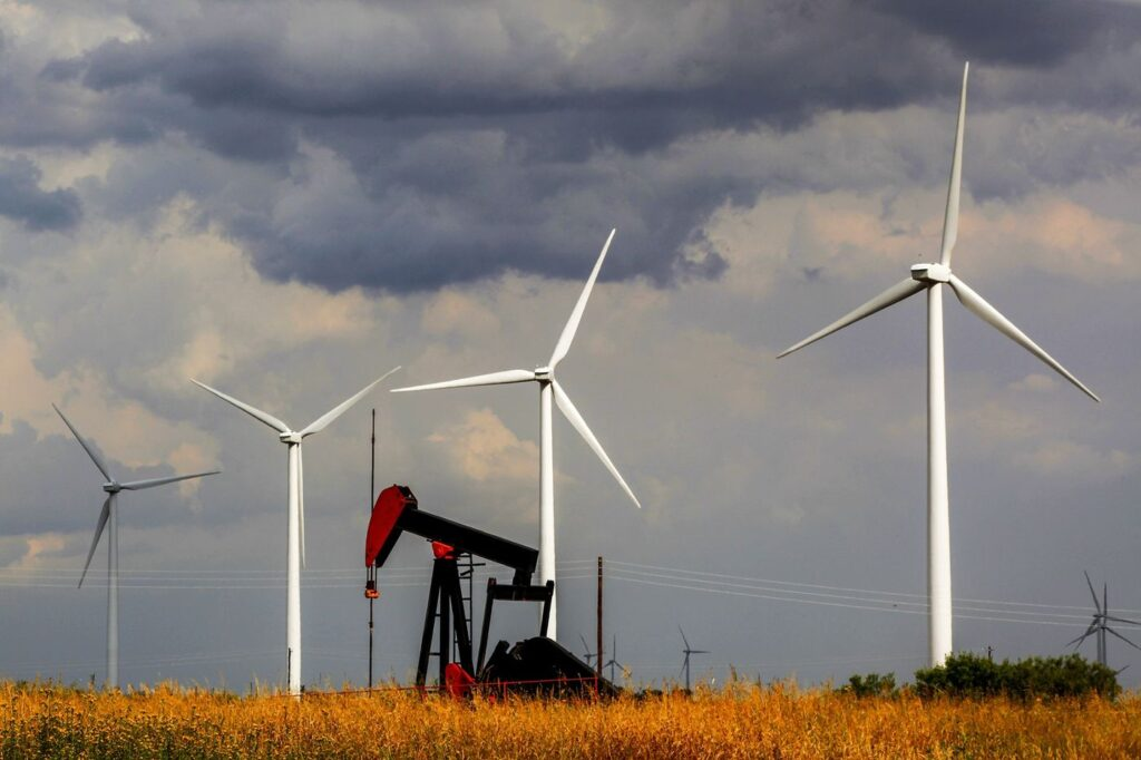 A pumpjack in front of wind turbines in West Texas. Photographer: Orjan F. Ellingvag/Corbis News